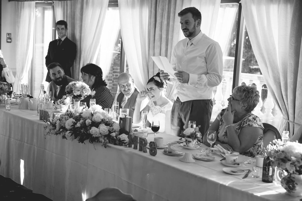 bride laughing at groom speech in black and white