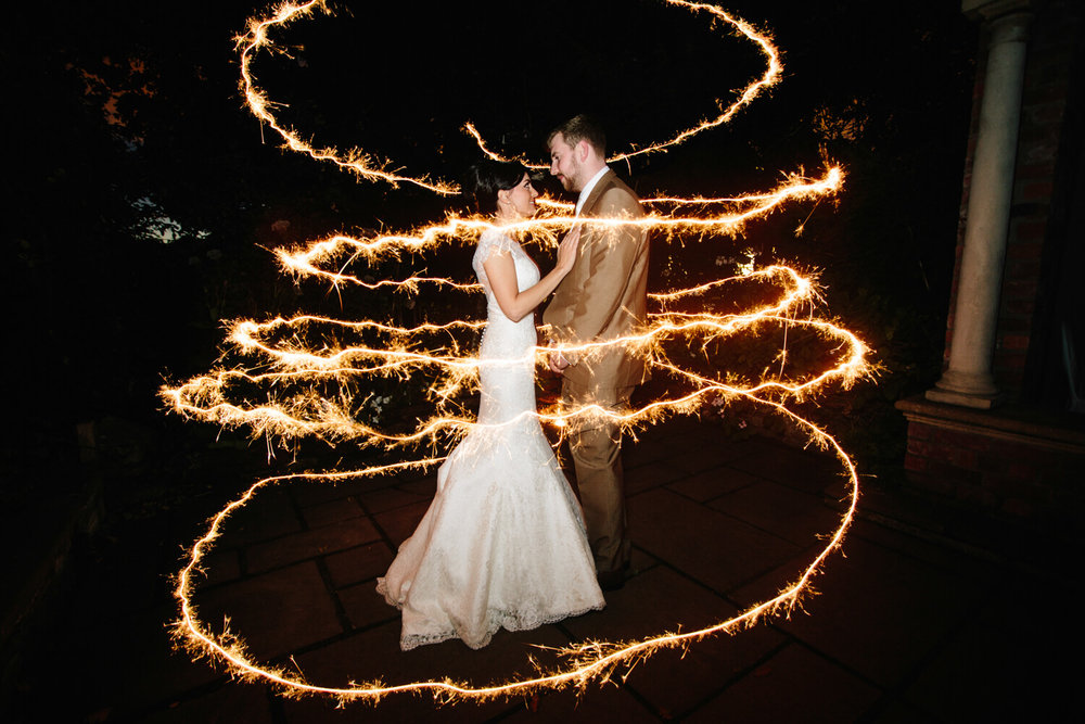sparkler image of bride and groom outside chapel