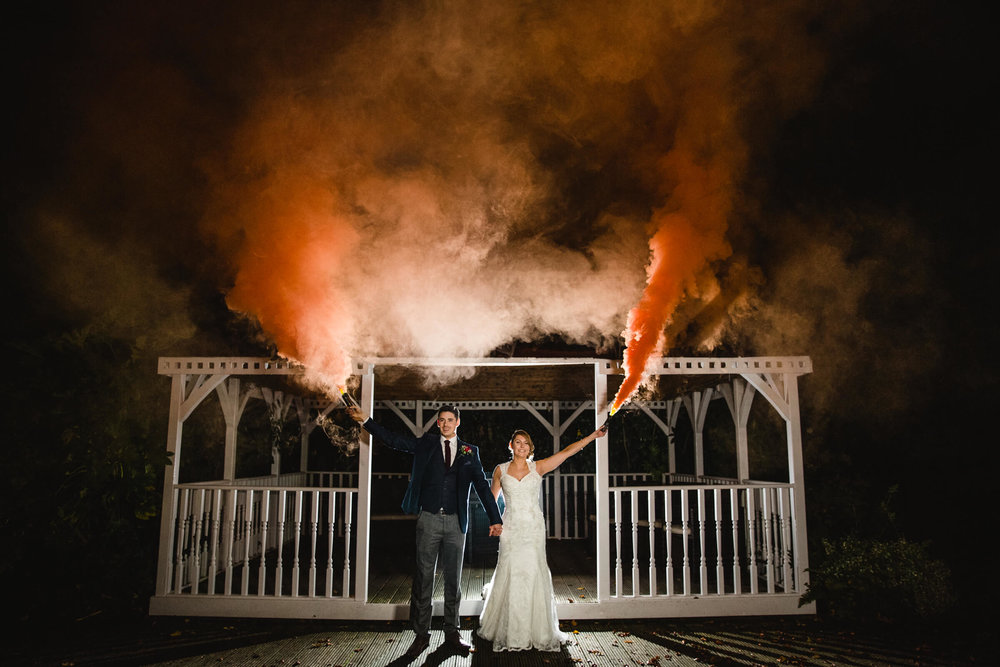 Newlywed couple holding orange smoke grandes in front of white wedding pagoda