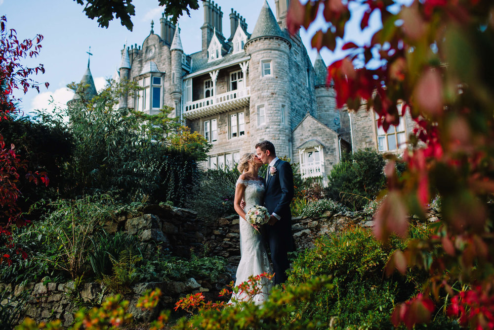 Newlywed couple in love in front of large castle and autumn leaves