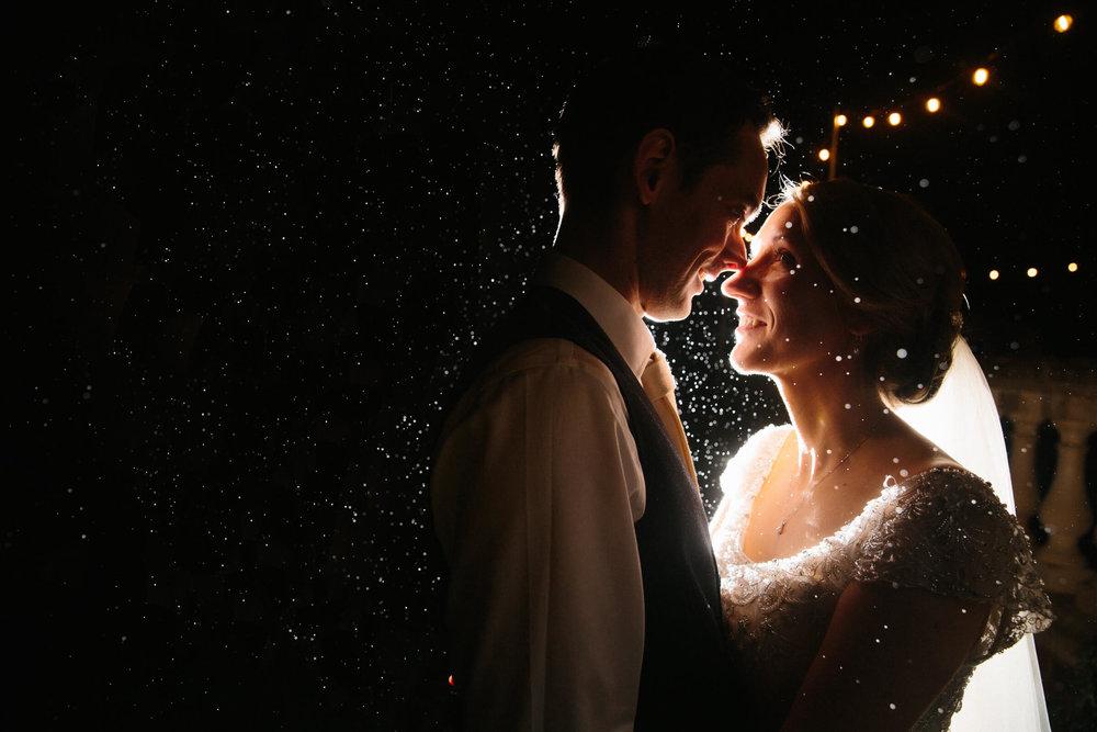 bride-groom-kissing-rain-with-festoon-lighting-lookbook.jpg