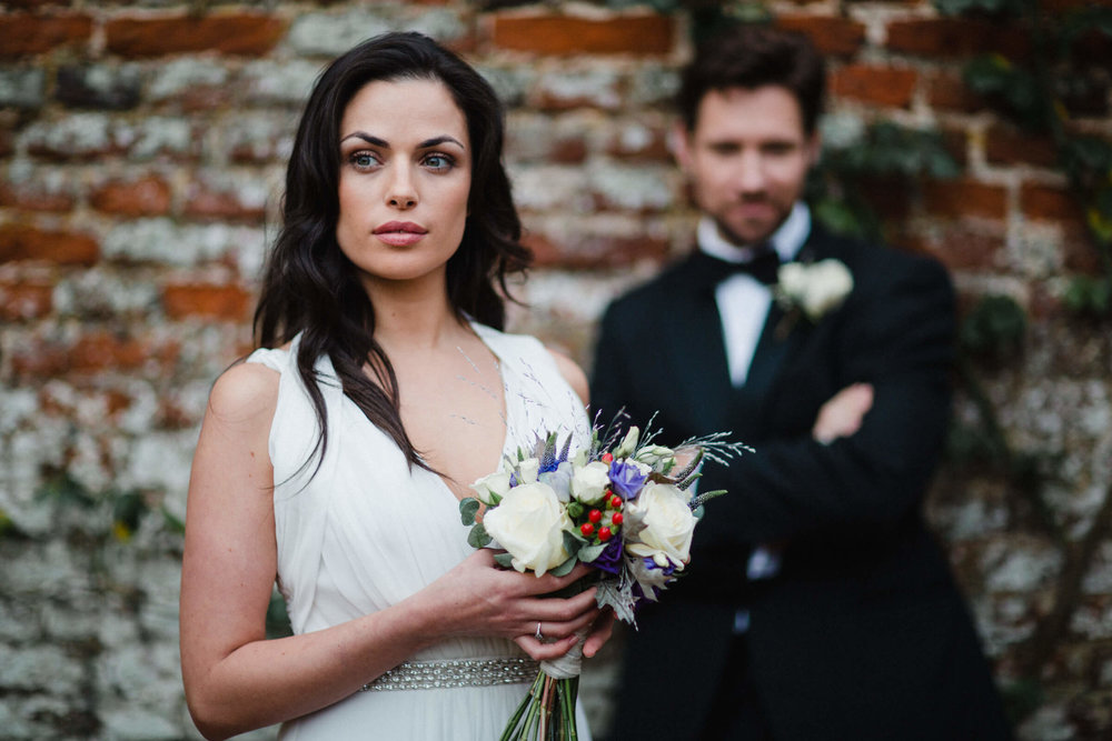 Bride holding bouquet looking away from groom leaning against red brick wall