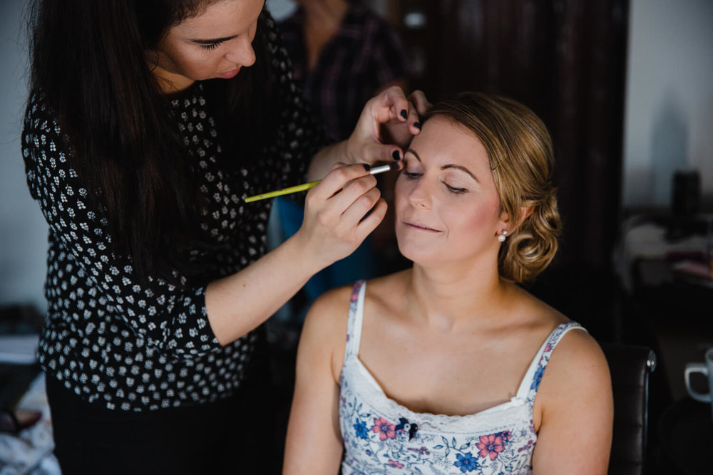 make up artist working on bride