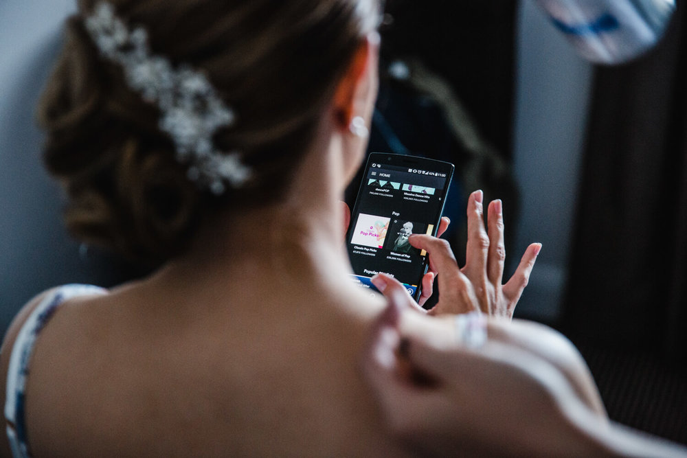 bride looking through phone selecting music