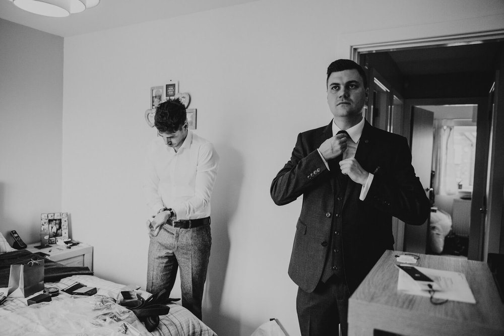 groom and best man preparing ties