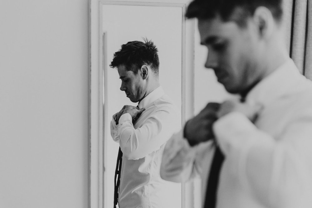 groom tying tie in mirror