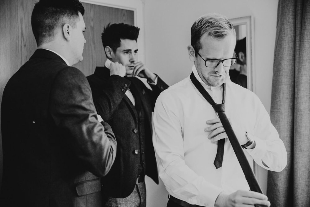 Groom and ushers tightening ties in the bedroom