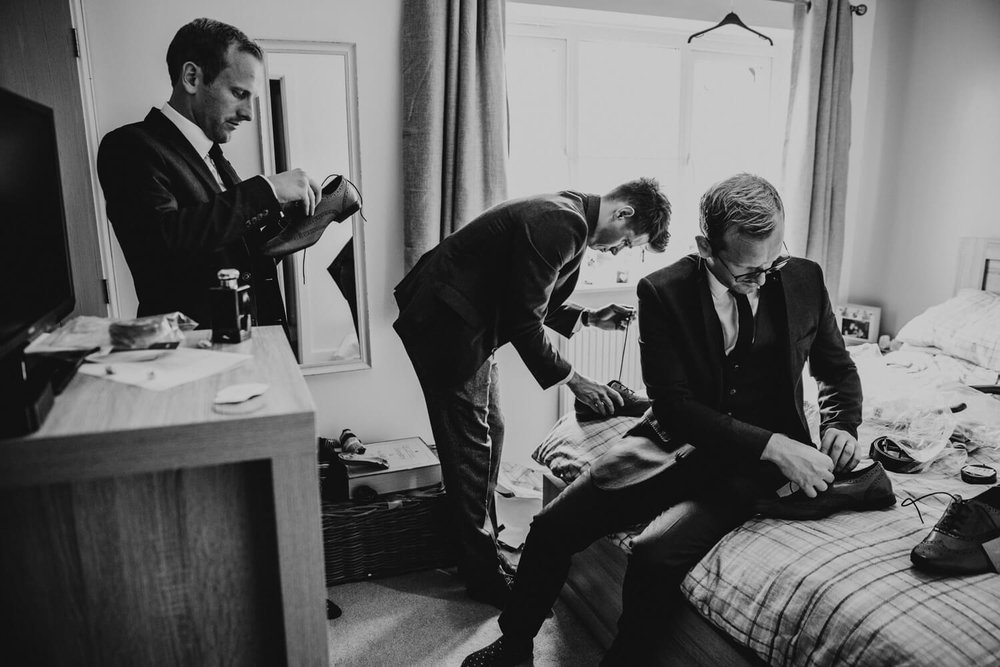 Groom and Ushers lacing up shoes on the bed