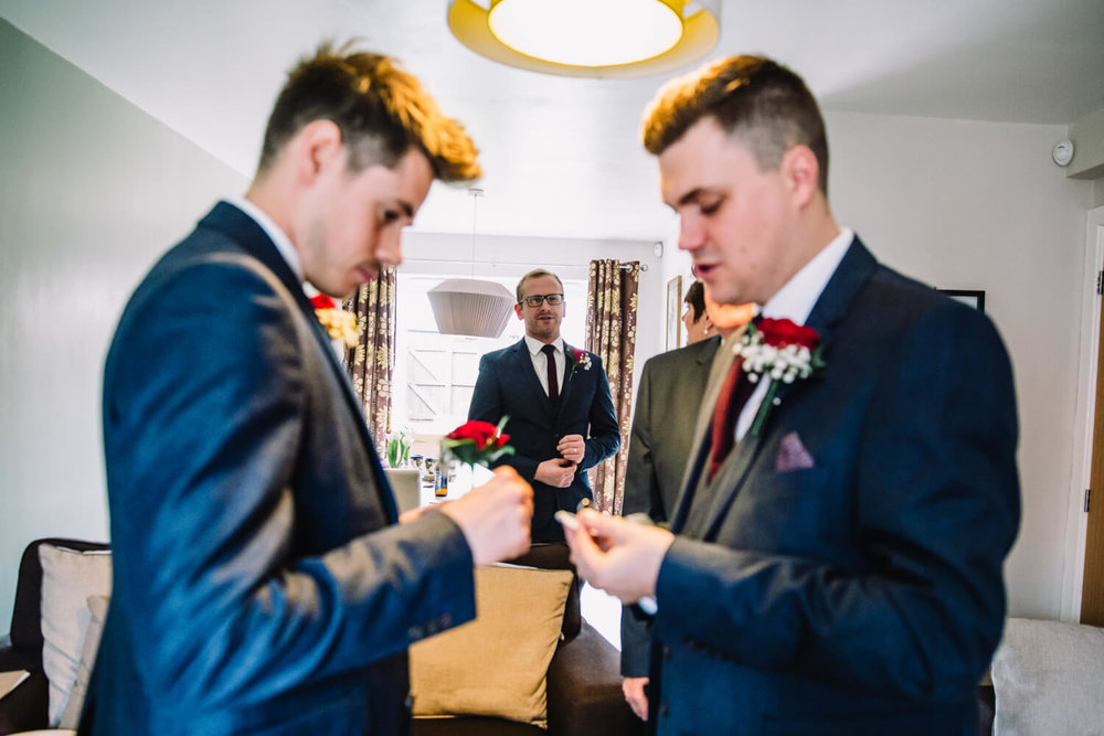 best man preparing button hole of suit