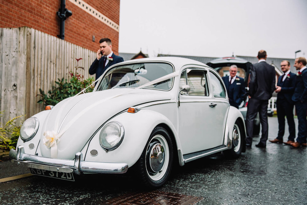 classic volkswagon beetle ready to take groom to ceremony