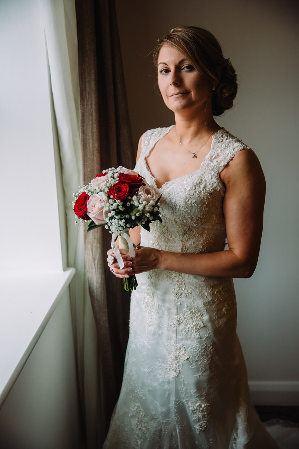 bride holding wedding flowers at window