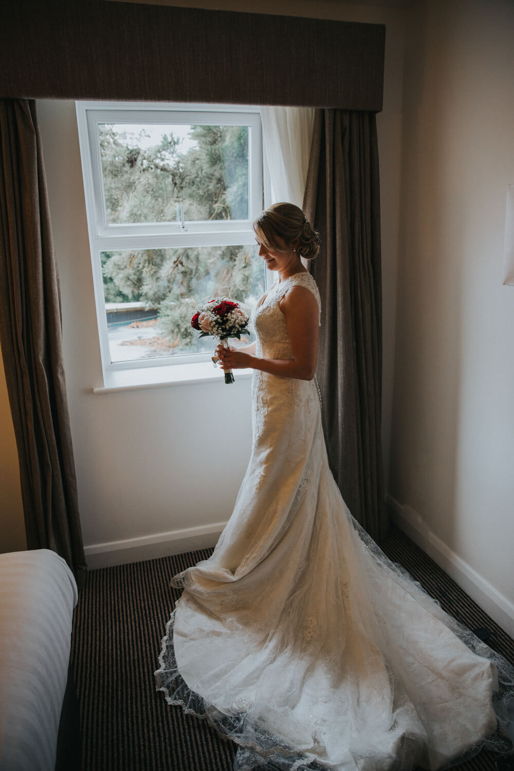 bride portrait in window holding bouquet