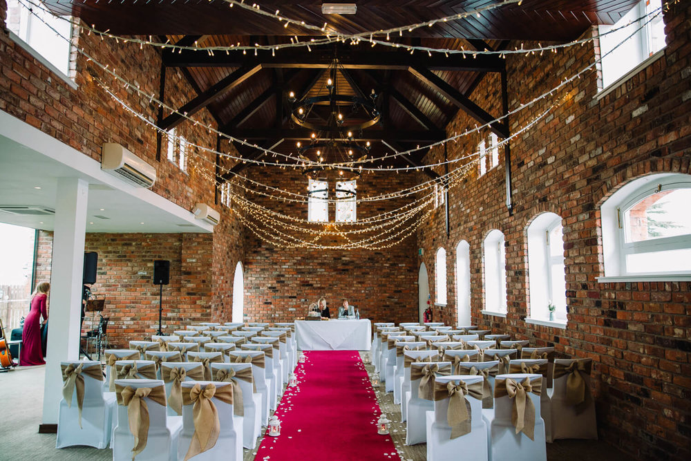 fairy light ceremony room with red carpet aisle