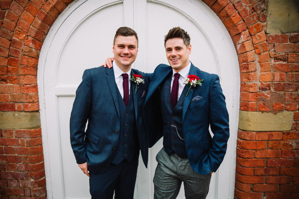 Groom and best man portrait in doorway