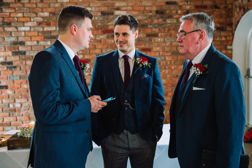 Groom waiting at end of aisle with best man