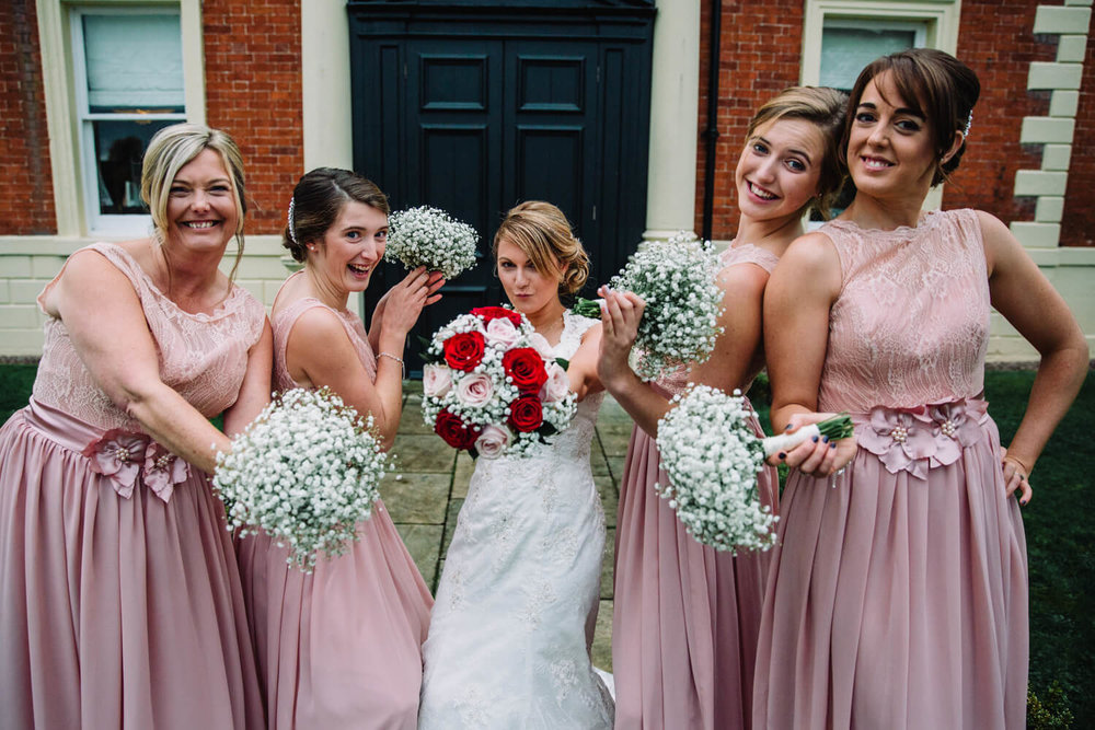 Bride and Bridesmaids with bouquets posing for camera