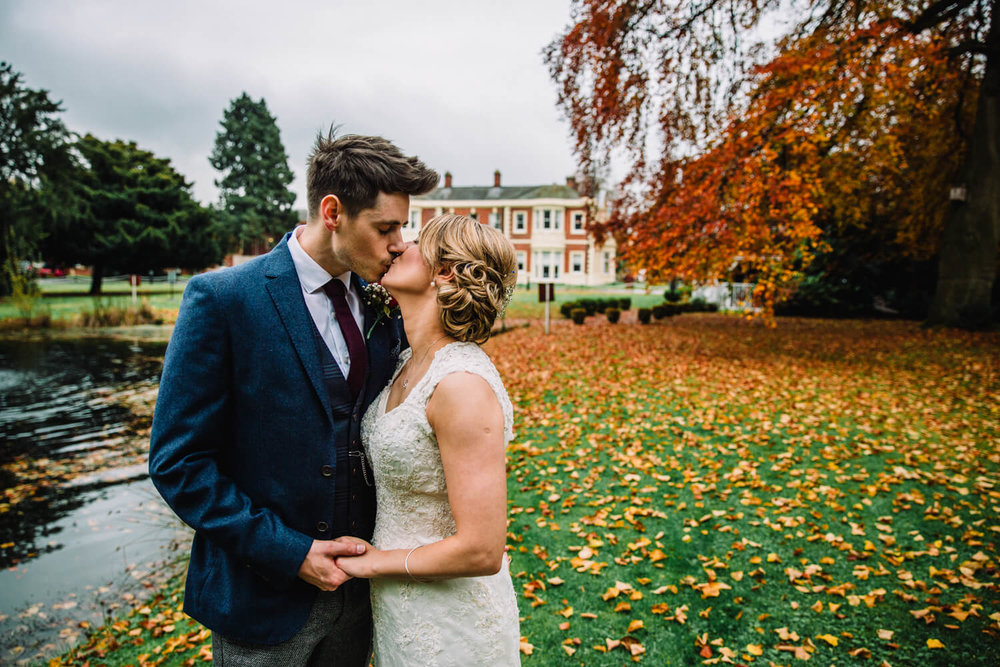 Kissing in front of pond in autumnal red and orange leaves in grounds of Hilton