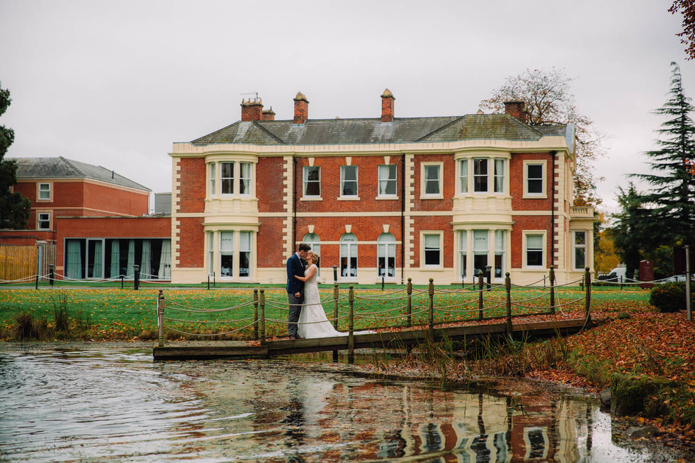 Bride and Groom kissing on jetty of pond with Hilton House in background