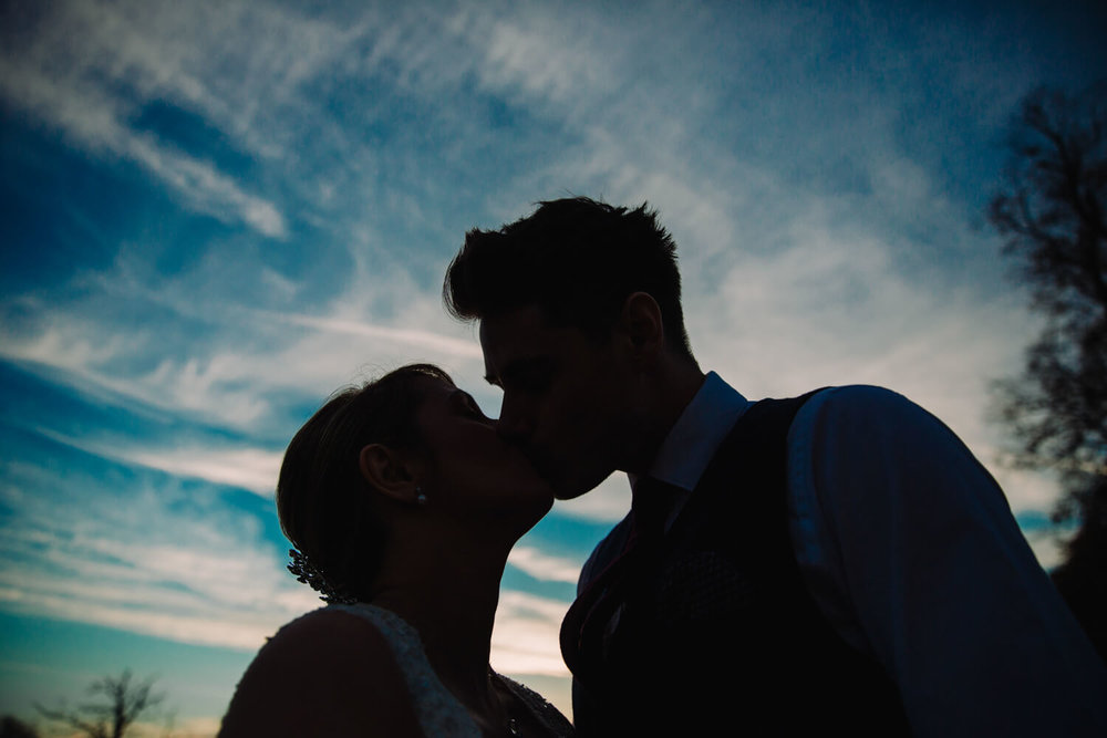 Bride and Groom silhouette portrait in blue sky