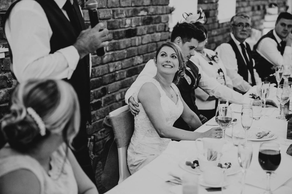 Bride looking on at brother during a moving speech