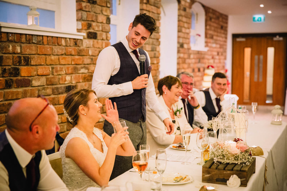 Groom laughing with Bride on top table of wedding breakfast