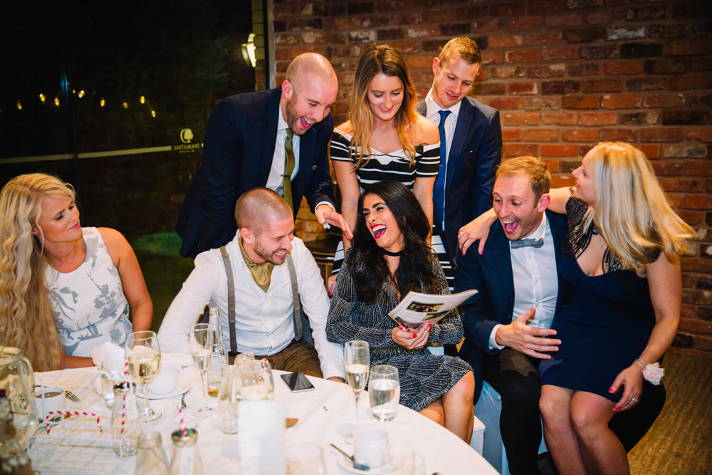 Group of friends laughing at pictures of groom given by best man