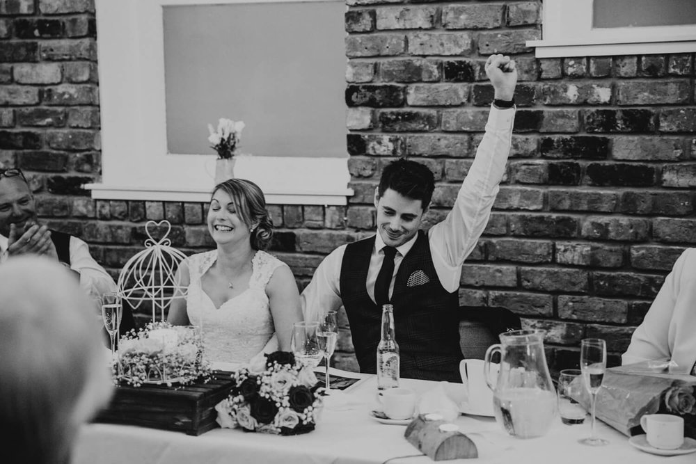 Groom fist pumping into the air and celebrating. Bride laughing
