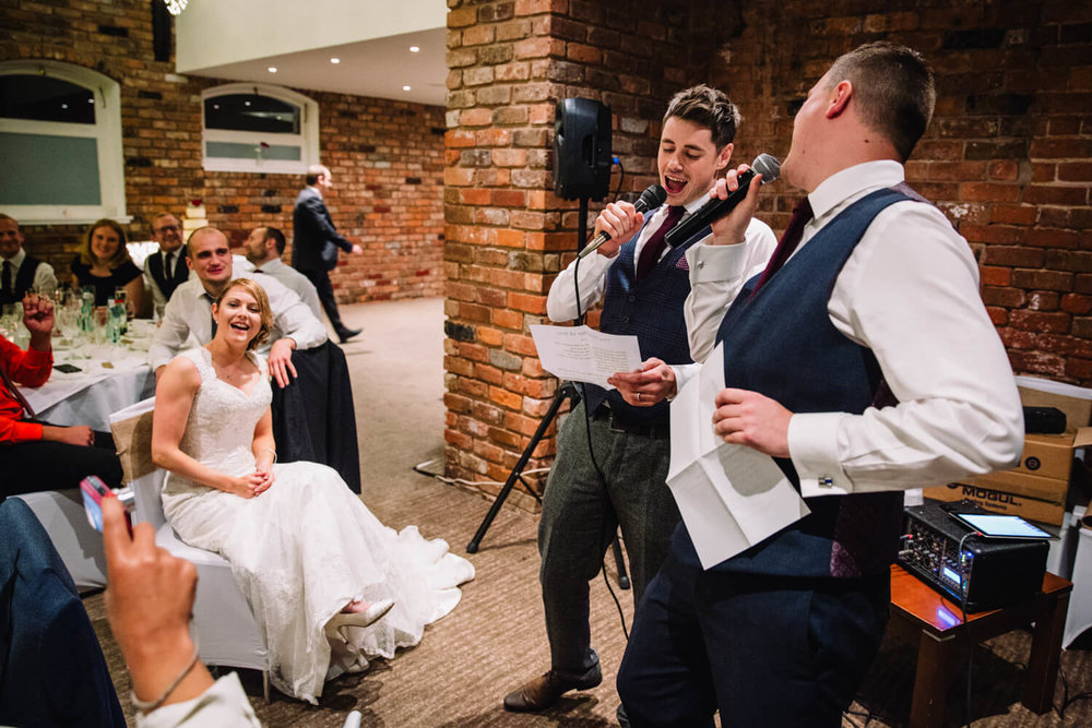 Groom and Best Man with microphones serenading guests