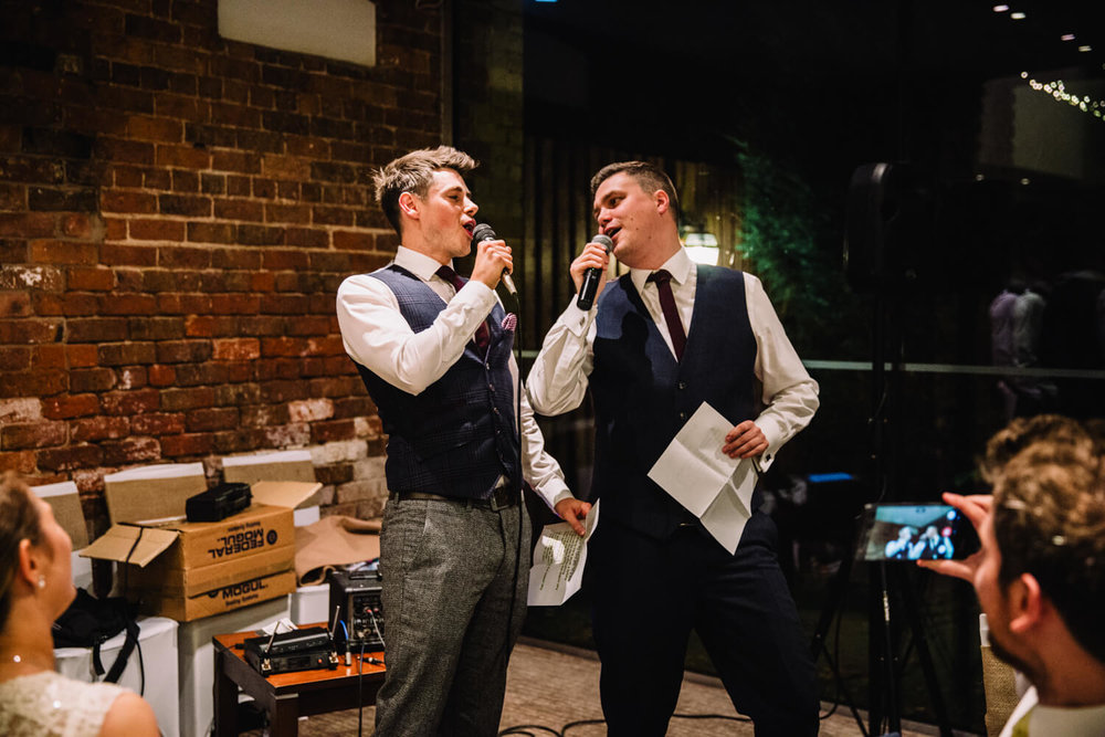 Groom and best man singing to bride
