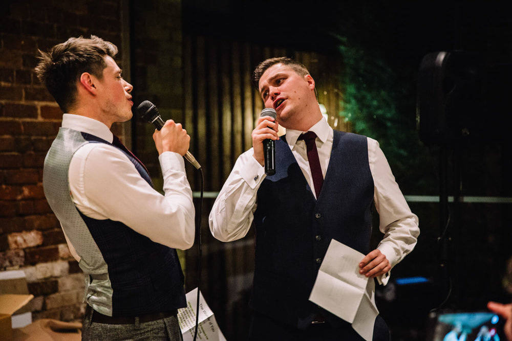 close up of groom and best man singing