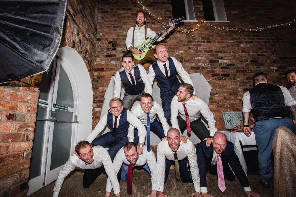 Groom and Groomsmen producing a human pyramid with usher on top playing an inflatable guitar