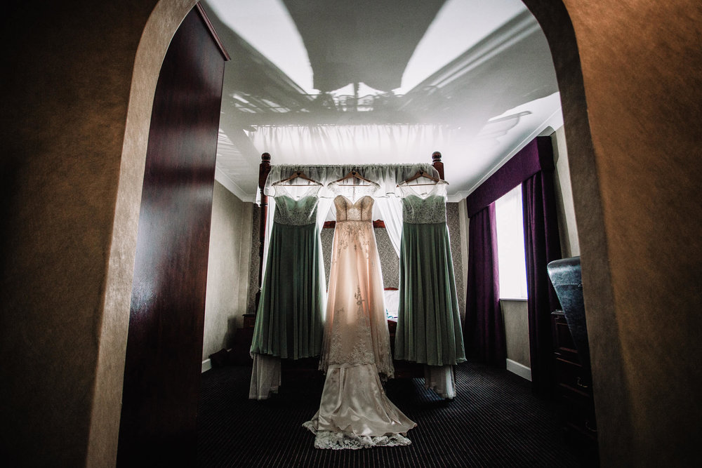wedding dress hung up on four poster bed with bridesmaid dresses