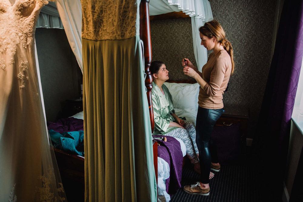 bridesmaid sat in window receiving make up