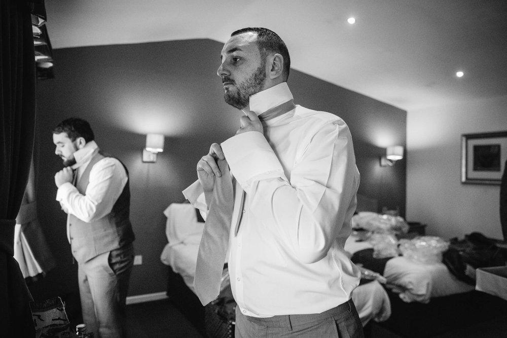 groom fastening tie in mirror