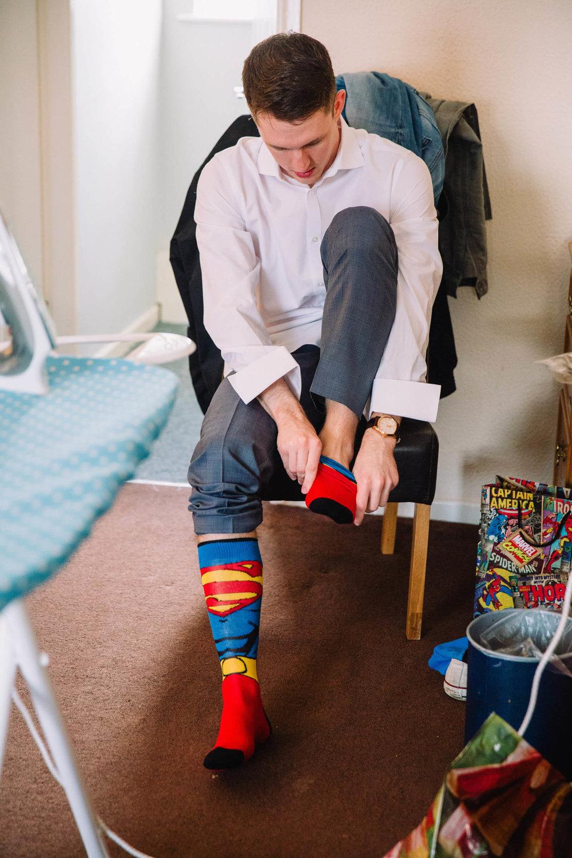 usher putting on superhero socks