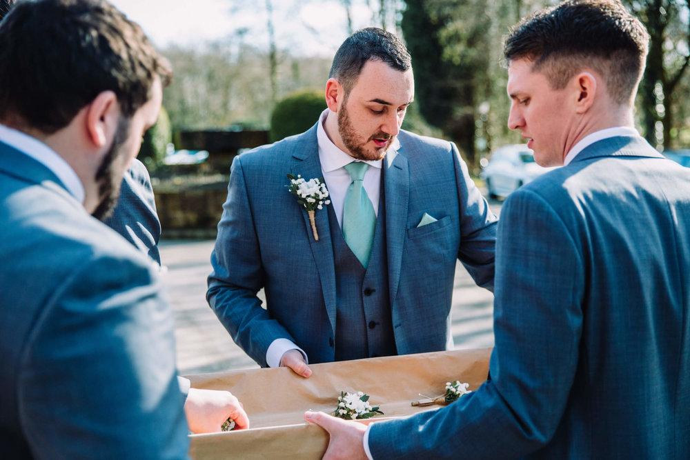 groom outside arranging pinhole flowers