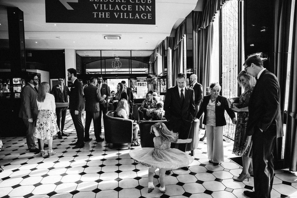 black and white of guests waiting in hotel lobby with flowergirl