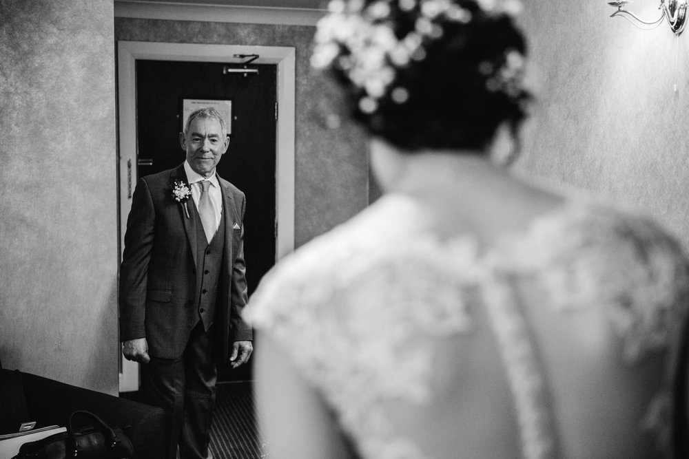 father of bride looking on at dress for the first time