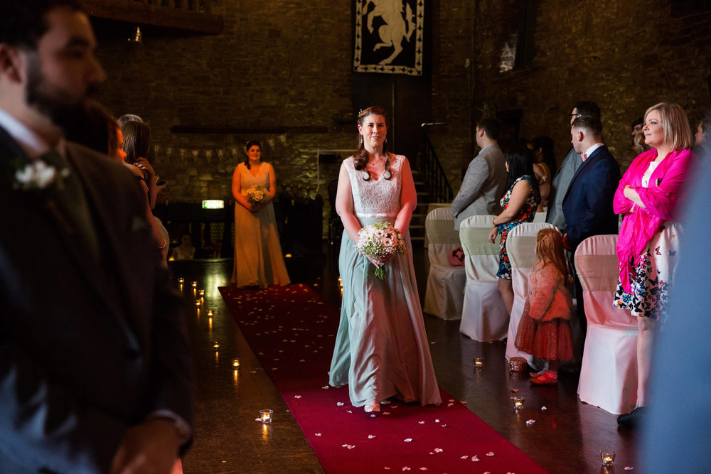 bridesmaid walking down aisle holding bouquet