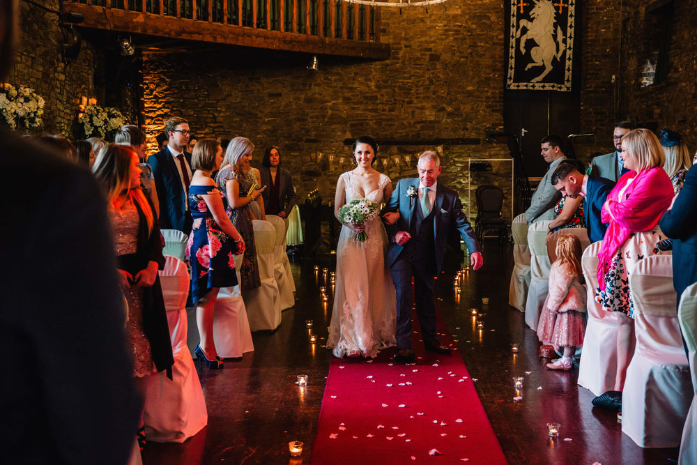 bride with father walking down the aisle with guests looking on