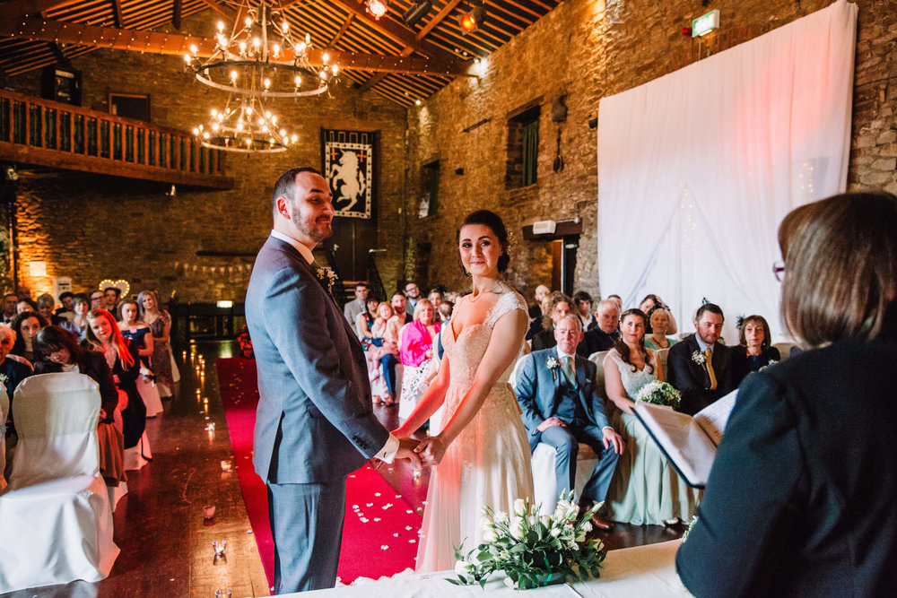 bride and groom saying vows in the medieval banqueting hall with draped chandeliers