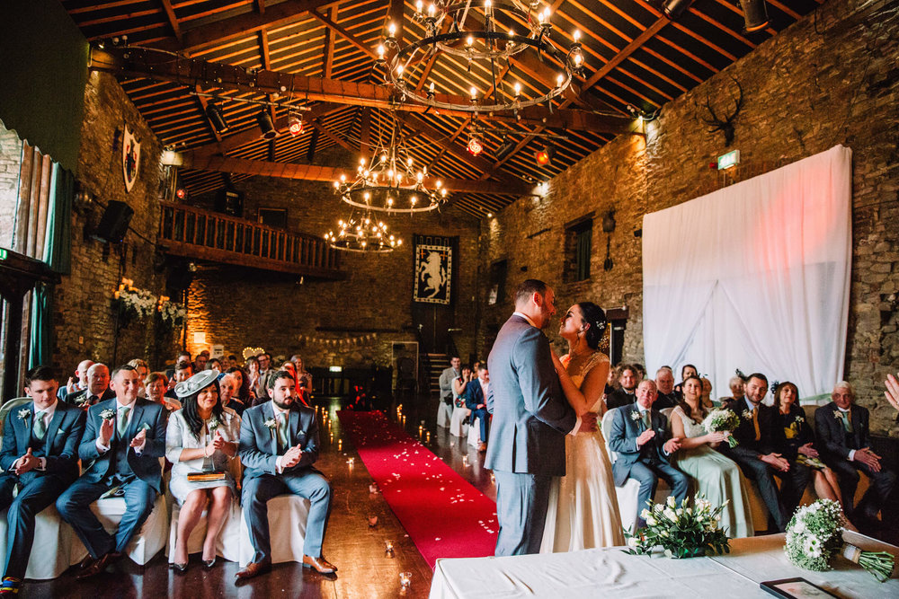 bride and groom saying vows in banqueting hall