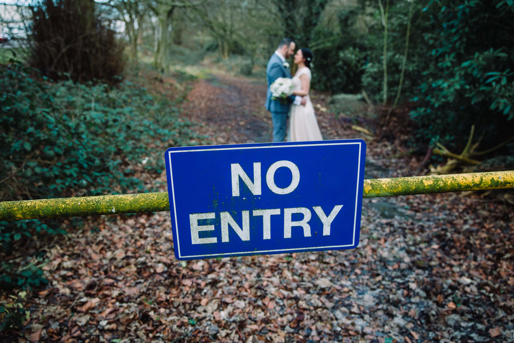 bride and groom portrait in front of a no entry sign