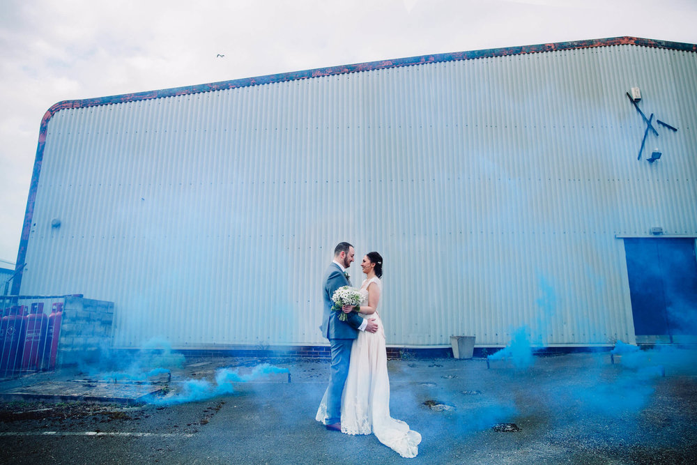 blue smoke grenade portrait in front of warehouse
