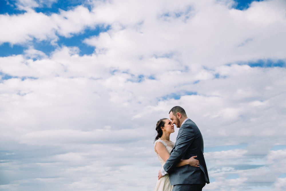 blue sky and cloud portrait for bride and groom holding each others arms