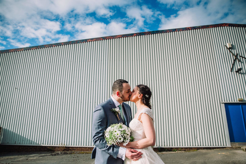 colour portrait in carpark of newlyweds in front of warehouse
