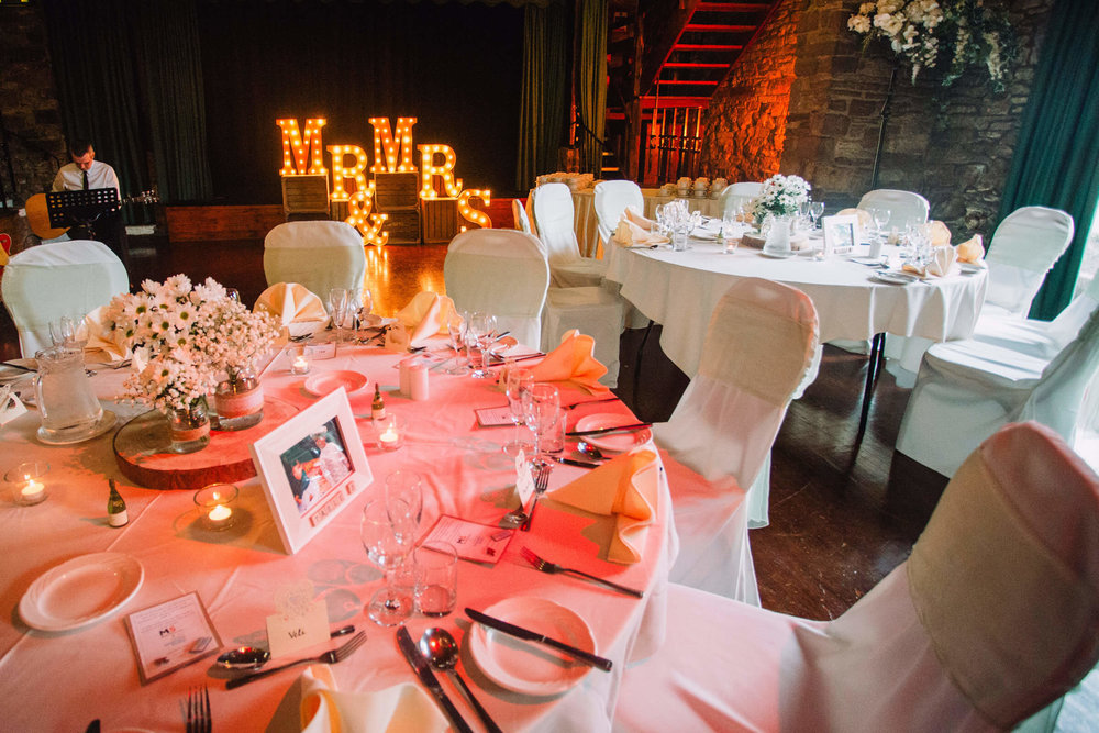 close up of wedding breakfast table with light up letters in background