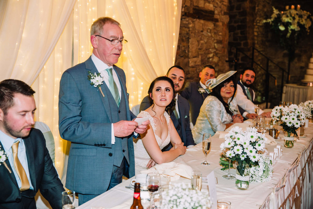 bride looking on to father during speeches