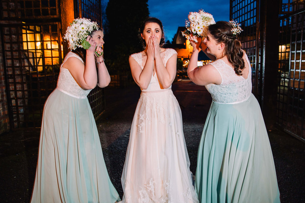 bridesmaids with bouquets and a shocked bride