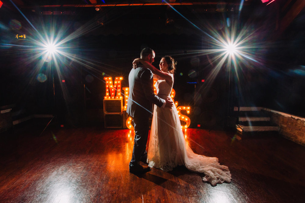 first dance of newlyweds in front of light up letters